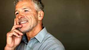 stock-footage-closeup-of-happy-middle-aged-man-daydreaming-against-grunge-background